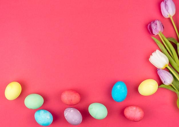 Uova di pasqua con tulipani luminosi sul tavolo rosso