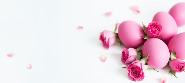 Uova di pasqua decorative e rose rosa uova di pasqua rosa su sfondo chiaro. biglietto di auguri