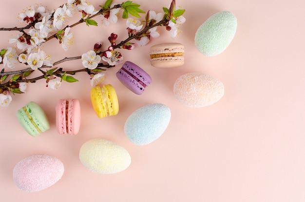 Uova di pasqua decorative multicolori e macarons dolci o amaretti decorati. vista dall'alto