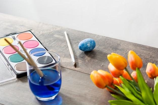 Uova di pasqua di verniciatura sulla tavola di legno