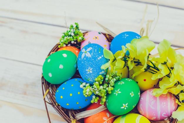 Uova di pasqua dipinte nei colori pastelli su fondo di legno bianco.