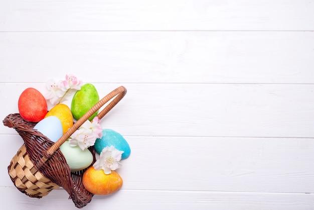 Uova di pasqua dipinte variopinte in canestro marrone