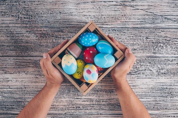 Uova di pasqua distese in scatola di legno con le mani di man_s su fondo di legno.
