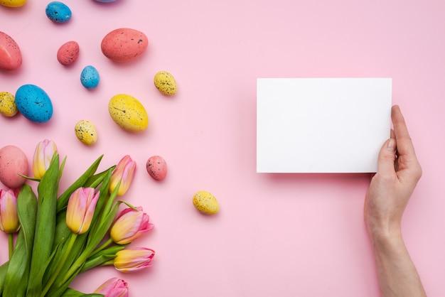 Uova di pasqua e cartolina d'auguri sulla tavola rosa
