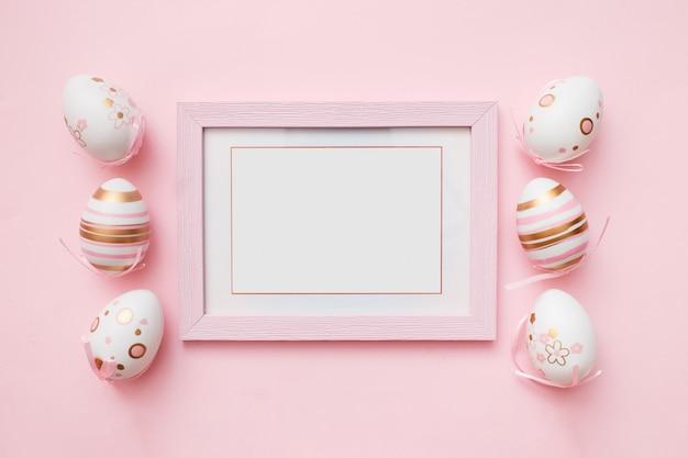 Uova di pasqua e cornice bianca sulla rosa
