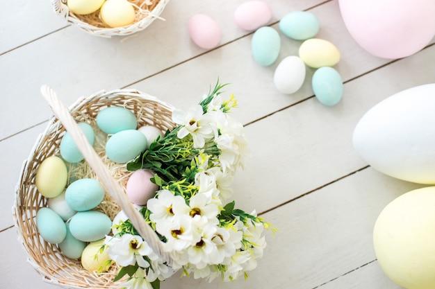 Uova di pasqua e fiori colorate in cestini di vimini. copia spazio - concetto di pasqua
