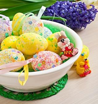 Uova di pasqua e fiori su fondo di legno