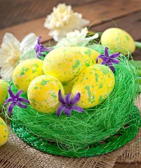 Uova di pasqua e fiori sulla tavola di legno