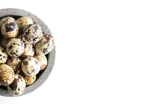 Uova di pasqua e piume di quaglie in ciotola ceramica su bianco