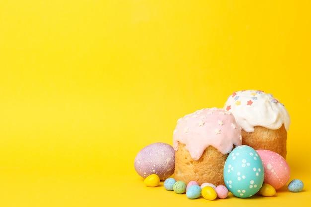 Uova di pasqua e torte su superficie gialla