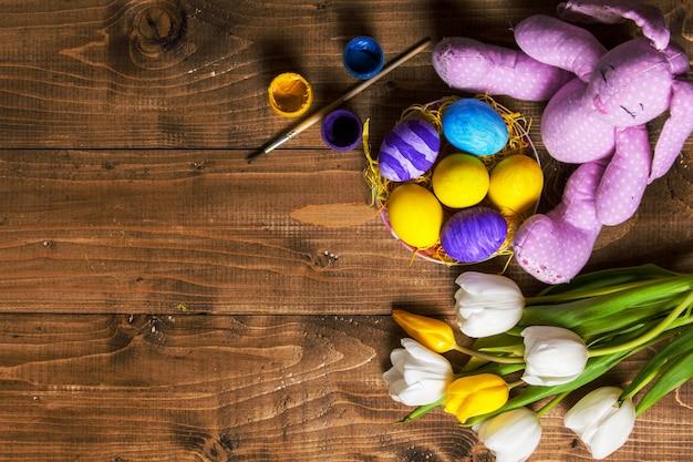 Uova di pasqua e tulipani sulle plance di legno, coniglietto
