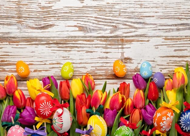 Uova di pasqua e tulipani sulle plance di legno