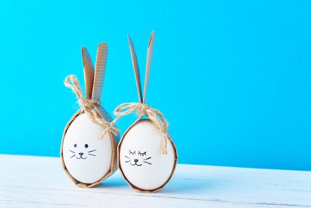 Uova di pasqua fatte in casa con facce e orecchie di coniglio su una parete blu
