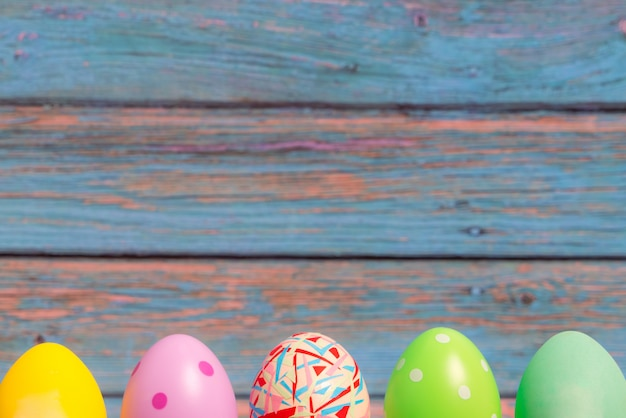 Uova di pasqua felici che stanno con gli ambiti di provenienza di legno blu, decorazioni di festa