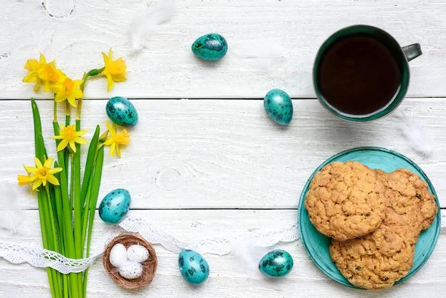 Uova di pasqua, fiori primaverili, tazza di caffè e biscotti per la colazione