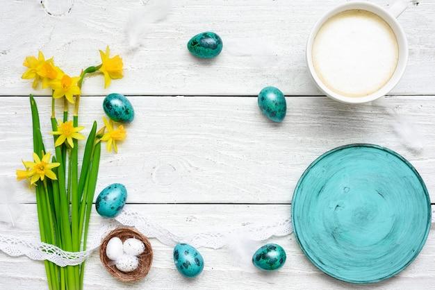 Uova di pasqua, fiori primaverili, tazza di cappuccino e piatto blu vuoto