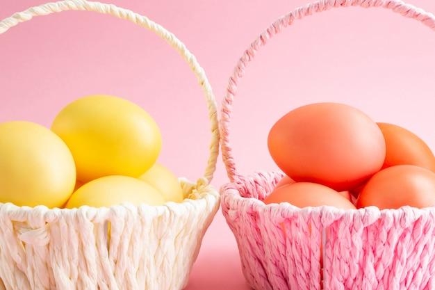 Uova di pasqua gialle e arancioni in cesti colorati. sfondo rosa concetto di vacanza di pasqua.