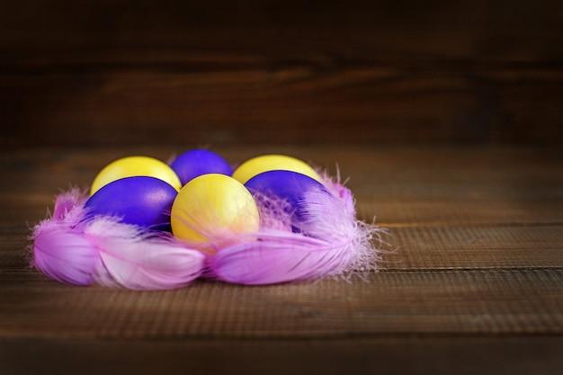 Uova di pasqua gialle e viola nel nido. concetto e buone vacanze di pasqua.