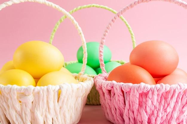 Uova di pasqua gialle, verdi e arancioni in cestini colorati. sfondo rosa concetto di vacanza di pasqua.