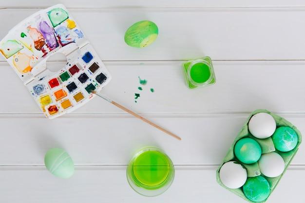 Uova di pasqua in contenitore tra tazze con liquido tintura vicino pennello con set di colori