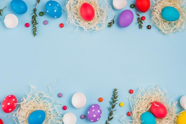 Uova di pasqua in nidi con rami di piante e caramelle