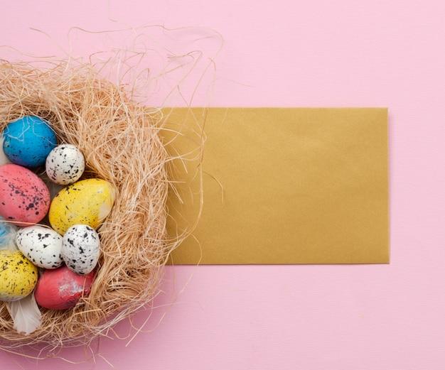 Uova di pasqua in nido e cartolina d'auguri