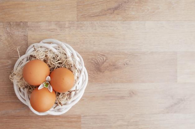 Uova di pasqua in nido sulla tavola rustica di legno, fondo di festa per la vostra decorazione. concetto di festa di pasqua e della primavera con lo spazio della copia.