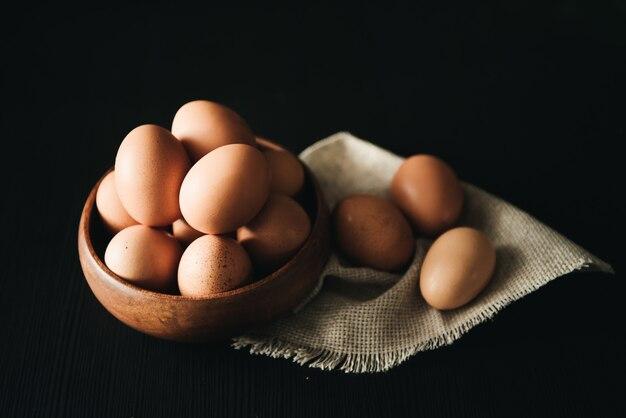 Uova di pasqua in piatto di legno su fondo nero. cibo salutare