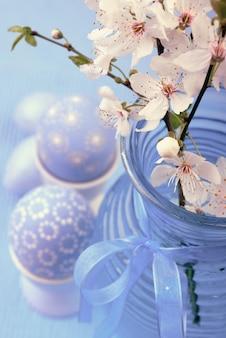 Uova di pasqua in portauova con fiori di ciliegio in vaso di vetro