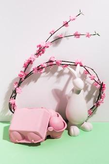 Uova di pasqua in rack con figurina di coniglio e fiori