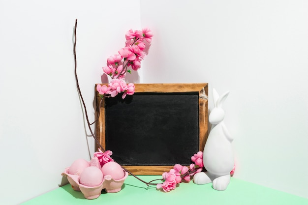 Uova di pasqua in rack con lavagna e fiori sul tavolo