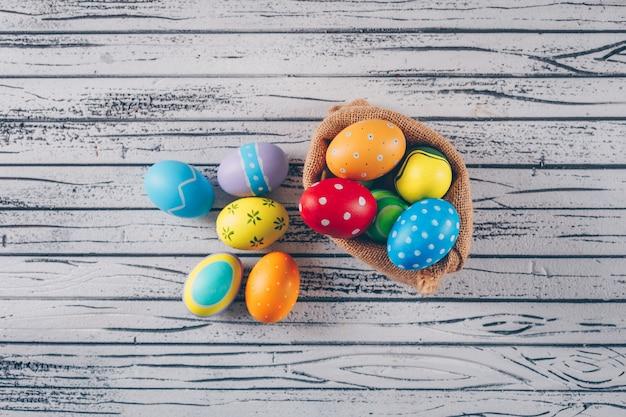 Uova di pasqua in sacco su fondo di legno leggero.