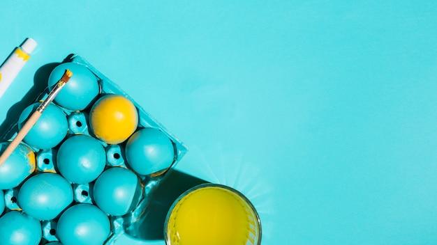 Uova di pasqua in scaffale con pennello e bicchiere d'acqua sul tavolo blu