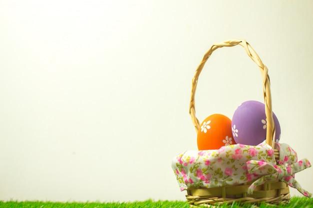Uova di pasqua in un cestino di tessuto di legno su una priorità bassa bianca.