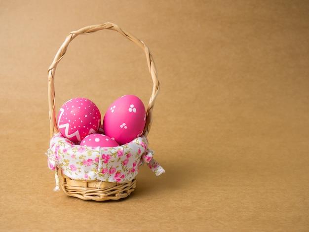 Uova di pasqua in un cestino di tessuto di legno su una priorità bassa marrone
