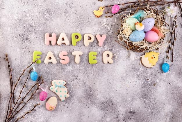 Uova di pasqua in un nido di erba e biscotti lustrati fatti in casa su uno sfondo di pietra, piatto posare