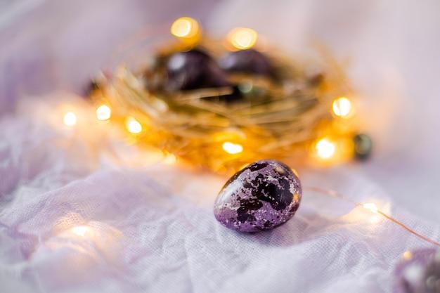 Uova di pasqua in un nido su una parete leggera circondata da luci festive e lampadine.