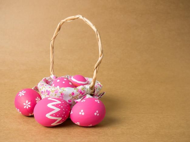 Uova di pasqua in un tessuto di cestino di legno