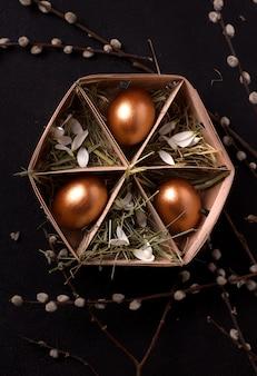 Uova di pasqua in una scatola con fieno