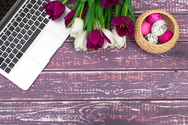 Uova di pasqua, laptop mockup e bouquet di tulipani.