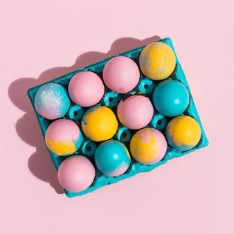 Uova di pasqua luminose in rack blu sul tavolo rosa