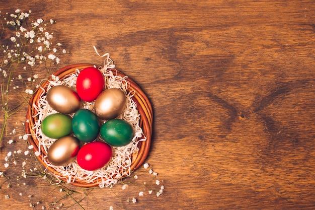 Uova di pasqua luminose sul piatto con orpelli vicino alle piante