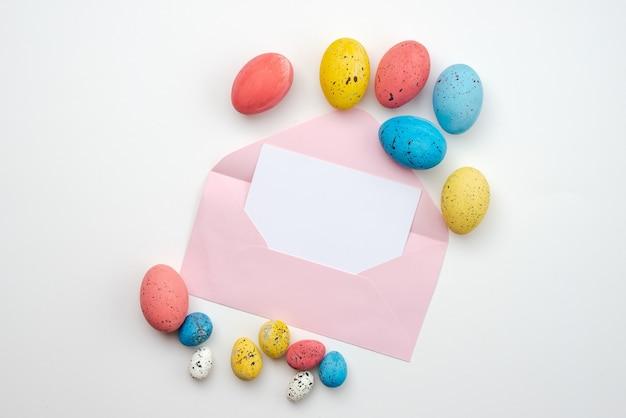 Uova di pasqua meravigliosamente colorate e una bella busta vuota