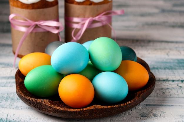 Uova di pasqua multicolori su un piatto e sui dolci di pasqua