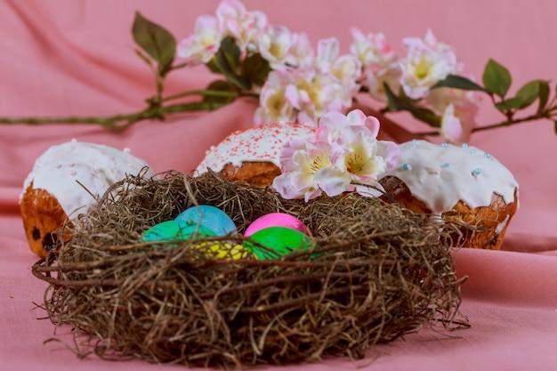 Uova di pasqua nel cesto della torta di pasqua con decorazioni colorate in un arcobaleno di colori