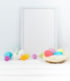 Uova di pasqua nel nido con cornice vuota sul tavolo
