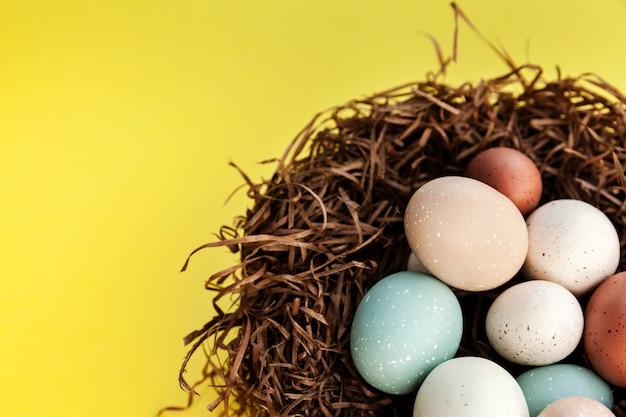 Uova di pasqua nel nido su fondo giallo con lo spazio della copia a sinistra