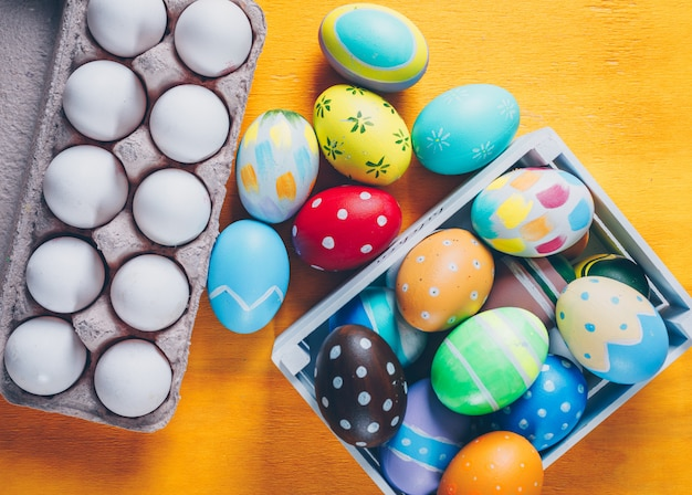 Uova di pasqua nella vista superiore del cartone dell'uovo e della scatola di legno su fondo di legno giallo
