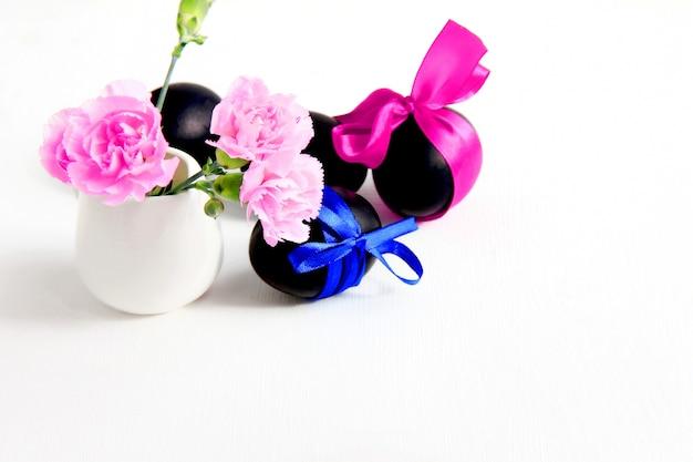 Uova di pasqua nere e fiori di garofano rosa su sfondo bianco