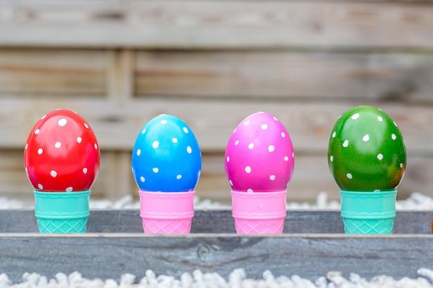 Uova di pasqua pastelli e colorati in coni del ghiaccio su un fondo di legno.